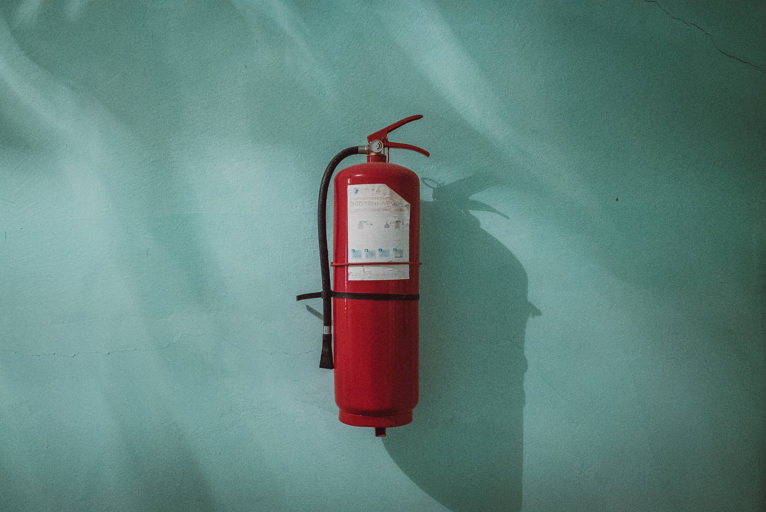 Fire extinguisher on blue wall